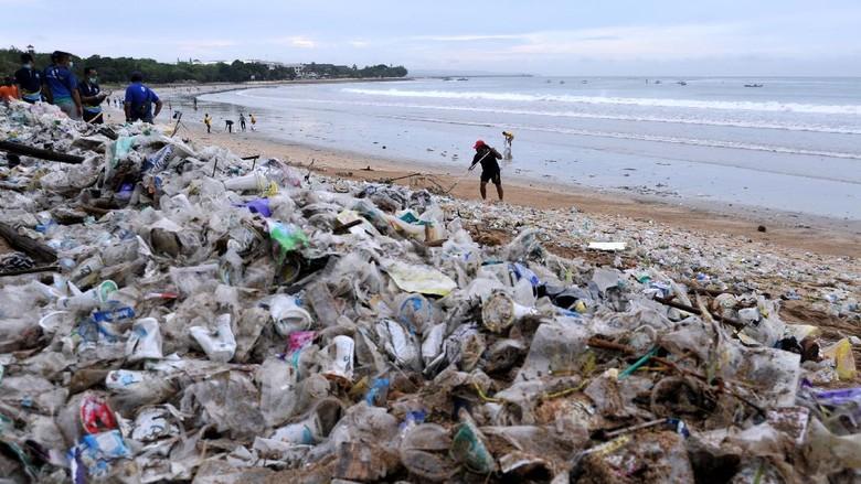 Relawan membersihkan sampah yang berserakan saat mengikuti aksi bersih sampah di Pantai Kuta, Badung, Bali, Rabu (6/1/2021). Kegiatan yang diikuti ratusan orang dari berbagai unsur masyarakat tersebut dilakukan untuk membersihkan sampah kiriman yang terbawa arus gelombang laut dan terdampar kawasan Pantai Kuta yang mengganggu aktivitas warga serta wisatawan. ANTARA FOTO/Fikri Yusuf/aww.