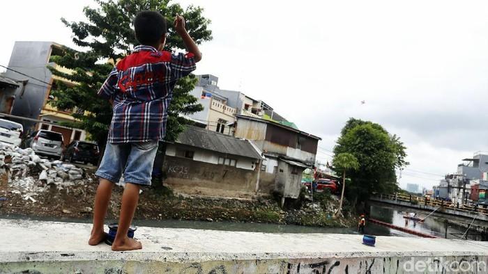 Minimnya lahan bermain, sejumlah anak bermain layangan di atas dinding turap Kali Cideng, Jalan Tanah Sereal, Tambora, Jakarta Barat, Rabu (6/1/2021).