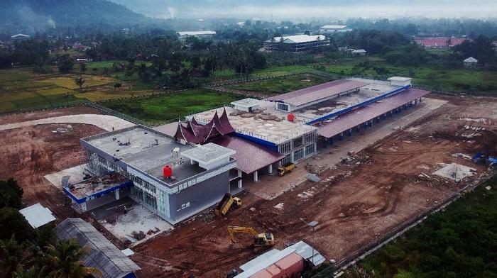 Warga melintas di depan terminal tipe A yang sedang dalam tahap penyelesaian pembangunan di Anak Air, Kecamatan Koto Tangah, Kota Padang, Sumatera Barat, Rabu (6/1/2021). Pembangunan dengan dana SBSN (Surat Berharga Syariah Negara) sebesar Rp72 miliar itu ditargetkan dapat diuji coba operasionalnya menjelang Idul Fitri 2021 yang diharapkan bisa membantu mengurai kemacetan di Kota Padang. ANTARA FOTO/Iggoy el Fitra/aww.