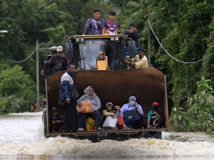 Residents ride a digger vehicle through floodwaters following heavy monsoon downpour in Lanchang, Malaysias Pahang state on January 6, 2021. (Photo by Mohd RASFAN / AFP)