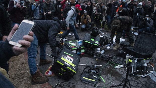 Demonstrators break TV equipment outside the the U.S. Capitol on Wednesday, Jan. 6, 2021, in Washington, during a chaotic protest aimed at thwarting a peaceful transfer of power. (AP Photo/Jose Luis Magana)