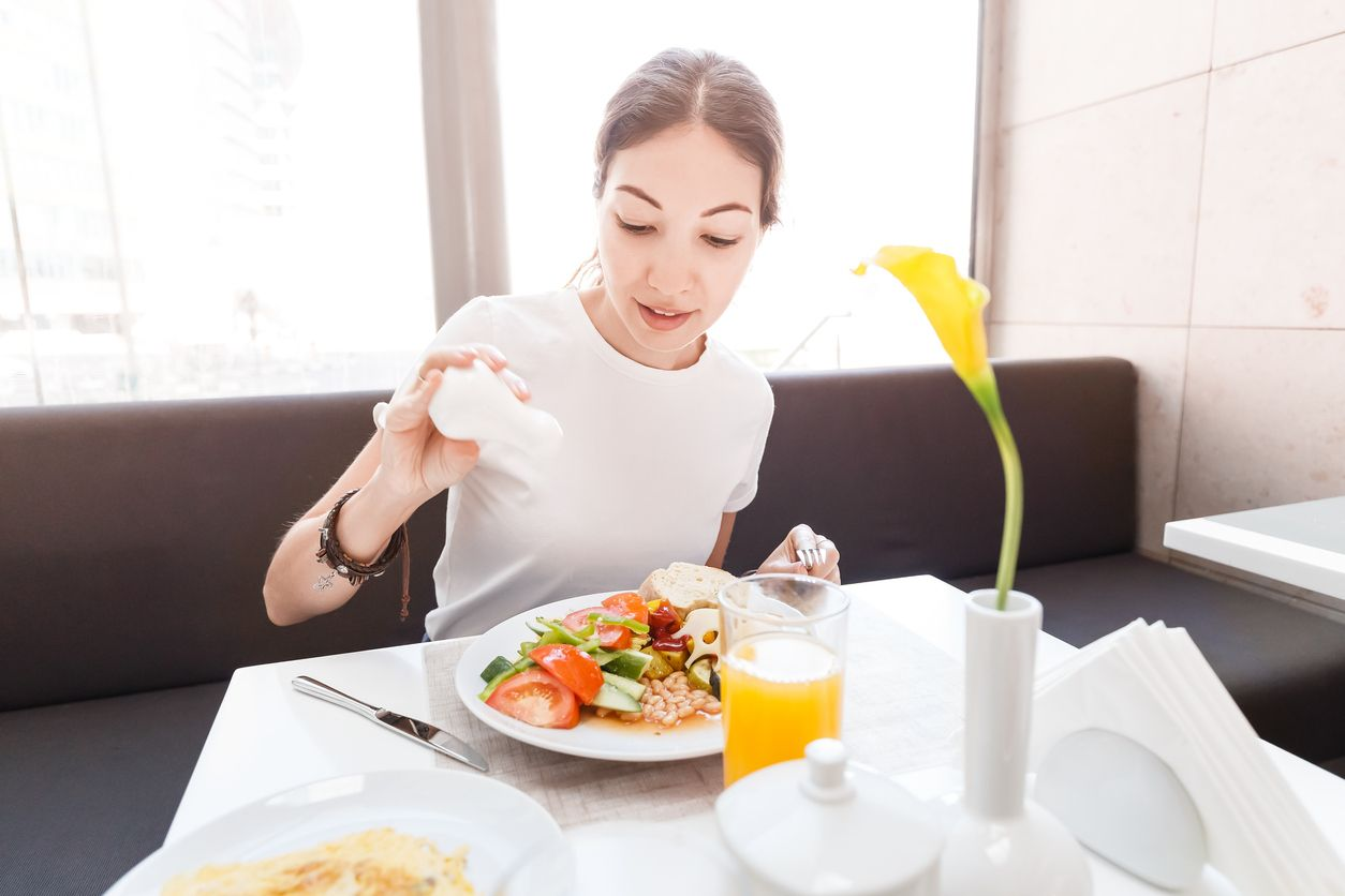 Asian woman in casual clothes having continental breakfast in hotel restaurant