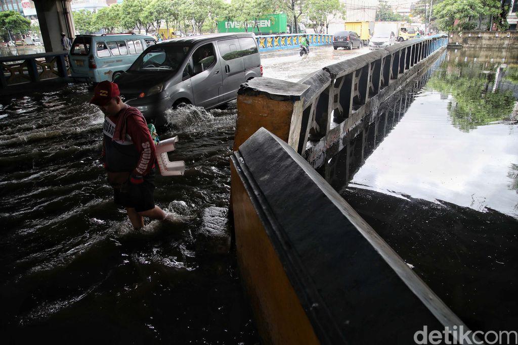 Sejumlah kendaraan menerobos genangan di Jalan Martadinata Ancol, Jakarta. Jalan ini tergenang akibat Kali Ancol meluap.