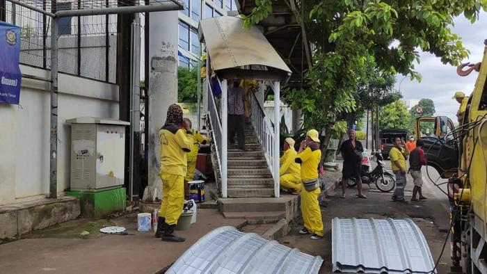 Pasukan kuning Dinas Bina Marga DKI Jakarta perbaiki JPO Matraman, Jakarta Timur.