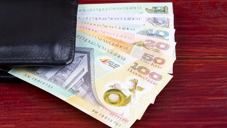 Money from Papua New Guinea in the black wallet on a wooden background