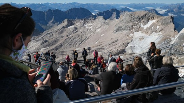 Pengunjung melihat sisa-sisa gletser Schneeferner Selatan dan gletser Schneeferner Utara yang semakin menipis dari puncak dataran tinggi Zugspitze, Garmisch-Partenkirchen, Jerman.