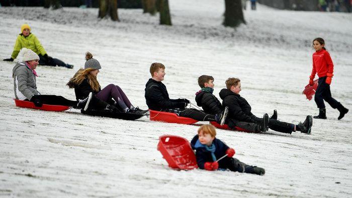Musim dingin bersalju yang tengah menyelimuti Skotlandia dimanfaatkan warga untuk bersantai dengan bermain seluncur dengan keluarga.