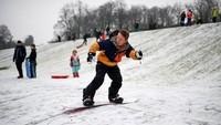 Seorang warga bermain snowboard di Queens Park, Glasgow, Skotlandia, Kamis (7/1/2021) waktu setempat. Jeff J Mitchell/Getty Images