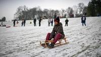 Warga memanfaatkan musim dingin bersalju untuk menghabiskan waktu dengan bermain seluncur. Jeff J Mitchell/Getty Images