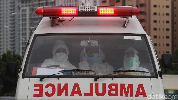 Para tenaga kesehatan dengan baju hazmat dan peralatan lengkap membawa pasien menggunakan mobil ambulans ke Rumah Sakit Darurat Penanganan COVID-19 (RSDP) Wisma Atlet, Jakarta, Sabtu (9/1/2021).