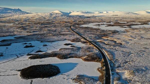 Tampak jalan raya A82 melintang di antara danau Lochan na Achlaise yang membeku.
