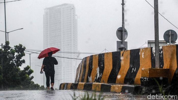 Warga beraktivitas di bawah guyuran air hujan di Kemayoran, Sabtu (9/1/2021). Badan Meteorologi, Klimatologi dan Geofisika (BMKG) memperkirakan wilayah Indonesia saat ini sudah memasuki puncak musim hujan. Periode ini akan bertahan hingga Februari mendatang.