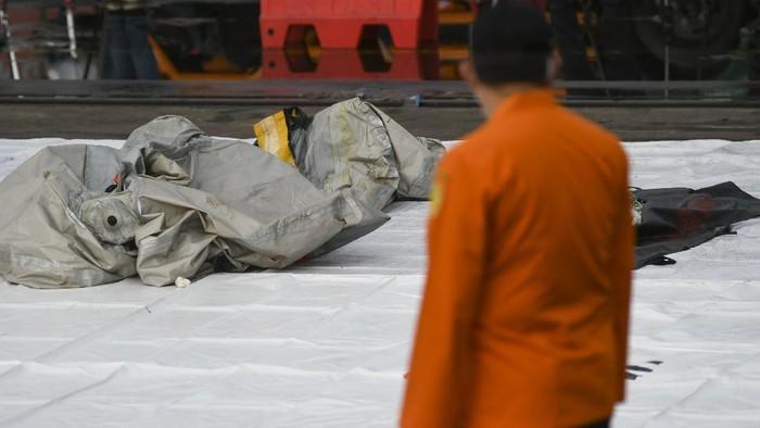 Petugas Basarnas memeriksa benda yang diduga serpihan dari pesawat Sriwijaya Air SJ 182 rute Jakarta - Pontianak yang hilang kontak di perairan Pulau Seribu, di Dermaga JICT, Jakarta, Minggu (10/1/2021). Pesawat Sriwijaya Air SJ 182 yang hilang kontak pada Sabtu (9/1) sekitar pukul 14.40 WIB di ketinggian 10 ribu kaki tersebut membawa enam awak dan 56 penumpang. ANTARA FOTO/Galih Pradipta/wsj.