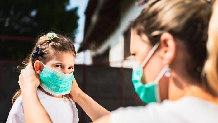 Single mother applying pollution mask to her daughter. They are outside.