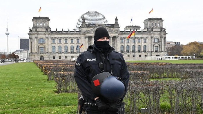 (FILES) This file photo taken on November 18, 2020 in Berlin shows a policeman standing guard in front of the Reichstag building housing the Bundestag (lower house of parliament) during a protest against measures imposed by the German government to limit the spread of the novel coronavirus. - Germany will examine boosting security for its parliament, the speaker of the house said Thursday, January 7, 2021, after the storming of the US Congress by violent protesters. Demonstrators against restrictions imposed by Chancellor Angela Merkels government to halt coronavirus transmission had attempted in the summer to enter the Reichstag parliament building, but were repelled by police forces. (Photo by Tobias SCHWARZ / AFP)