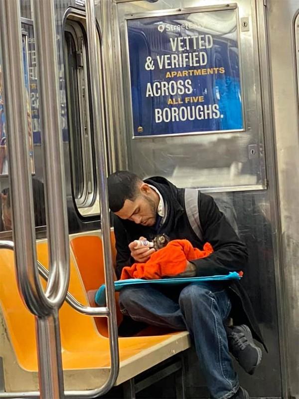 Adem banget nih lihat seorang pria memberi susu untuk kucing di subway.