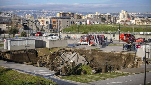 A view of the large sinkhole that opened overnight in the parking of Ospedale del Mare hospital in Naples, Italy, Friday, Jan. 8, 2021. A giant sinkhole opened Friday in the parking lot of a Naples hospital, forcing the temporary closure of a nearby residence for recovering coronavirus patients because the electricity was cut. (Alessandro Pone/LaPresse via AP)