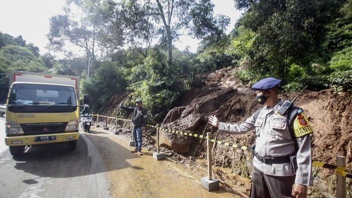 Petugas mengevakuasi tanah longsor di pinggir jalan utama Puncak, Gunung Mas, Cisarua, Kabupaten Bogor, Jawa Barat, Senin (11/1/2021). Longsor yang terjadi pada pukul 00.30 WIB tersebut disebabkan oleh intensitas hujan yang tinggi dan mengakibatkan penutupan sementara jalur Puncak untuk evakuasi material longsor yang menutupi jalan. ANTARA FOTO/Yulius Satria Wijaya/rwa.