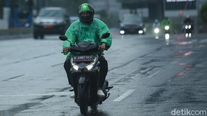 Pengendara ojek online melintas di jalan Sudirman, Jakarta, Selasa (12/1/2021). Pemberlakuan Pembatasan Kegiatan Masyarakat (PPKM) membuat orderan ojek online mulai sepi.