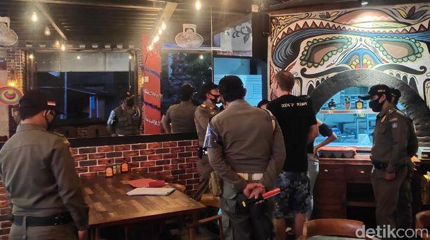 Satpol PP memaksa WNA untuk keluar dari restoran karena sudah lewati jam operasional 21.00 Wita (dok Istimewa)