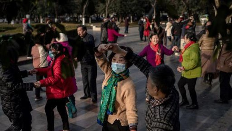 Elderly people dance in a public area along the Yangtze River in Wuhan on January 11, 2021, as the city marks the first anniversary of when China confirmed its first death from the COVID-19 coronavirus. (Photo by NICOLAS ASFOURI / AFP)