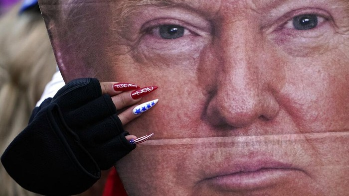 A woman holds a cut out of President Donald Trumps face Wednesday, Jan. 6, 2021, in Washington, at a rally in support of President Donald Trump called the