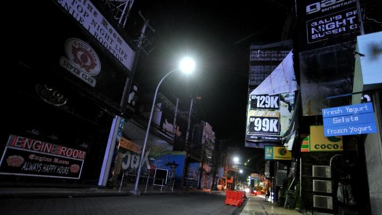 Suasana kawasan wisata Jalan Legian tampak sepi saat penerapan Pemberlakuan Pembatasan Kegiatan Masyarakat (PPKM) di Kuta, Badung, Bali, Selasa (12/1/2021). Seluruh kegiatan usaha di kawasan tersebut dibatasi operasionalnya hingga pukul 21.00 WITA saat penerapan kebijakan PPKM sebagai upaya untuk menekan penyebaran COVID-19. ANTARA FOTO/Fikri Yusuf/rwa.
