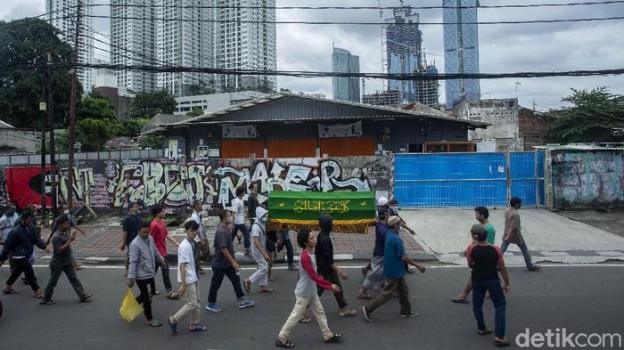 Warga turun ke jalan untuk mengiringi jenazah yang akan dimakamkan di kawasan Jakarta. Pandemi tak membuat tradisi mengiringi jenazah itu ditinggalkan warga.