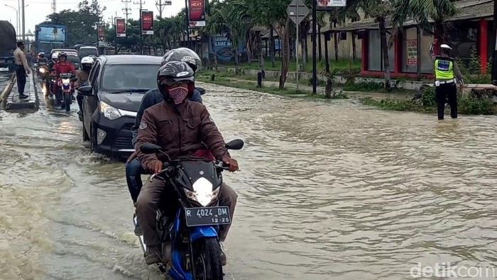 Jalur Pantura di Desa Kedungkelor, Kecamatan Warureja, Kabupaten Tegal, Jawa Tengah, tergenang banjir. Akibatnya lalin menjadi tersendat.