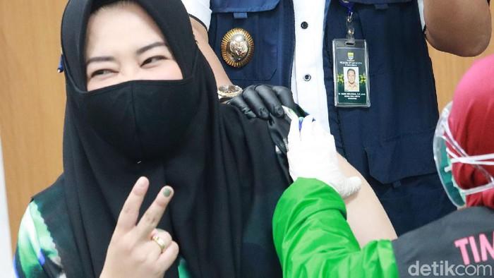 Risa Saraswati ikut kick off penyuntikan vaksin COVID-19 di RSKIA Kota Bandung. Novelis sekaligus YouTuber itu sempat mengacungkan dua jarinya saat disuntik.