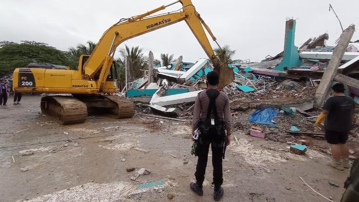 Petugas menggunakan alat berat memindahkan puing bangunan RS Mitra Manakarra yang rusak pascagempa bumi, di Mamuju, Sulawesi Barat, Jumat (15/1/2021). Petugas BPBD Sulawesi Barat masih mendata jumlah kerusakan dan korban akibat gempa bumi berkekuatan magnitudo 6,2 tersebut. ANTARA FOTO/Akbar Tado/wpa/hp.