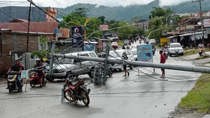 Warga melintasi tiang listrik yang melintang di jalan raya pascagempa bumi,  di Mamuju, Sulawesi Barat, Jumat (15/1/2021). Petugas BPBD Sulawesi Barat masih mendata jumlah kerusakan dan korban akibat gempa bumi berkekuatan magnitudo 6,2 tersebut. ANTARA FOTO/Akbar Tado/wpa/hp.