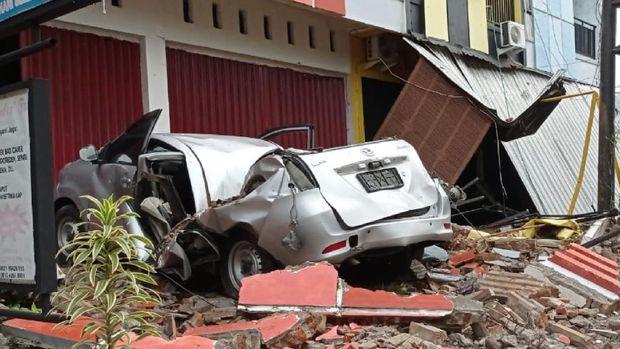 Sebuah mobil dan bangunan rusak akibat gempa bumi, di Mamuju, Sulawesi Barat, Jumat (15/1/2021). Petugas BPBD Sulawesi Barat masih mendata jumlah kerusakan dan korban akibat gempa bumi berkekuatan magnitudo 6,2 tersebut. ANTARA FOTO/Akbar Tado/wpa/hp.