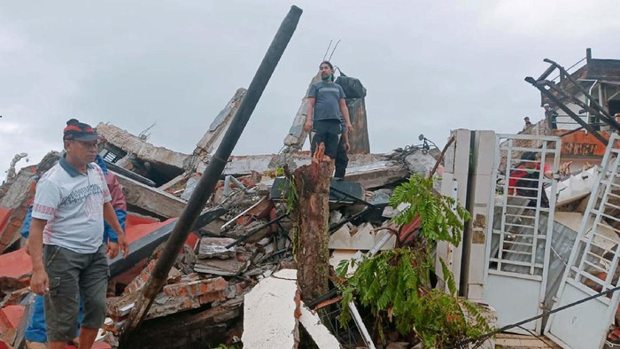 Residents inspect earthquake-damaged buildings in Mamuju, West Sulawesi, Indonesia, Friday, Jan. 15, 2021. A strong inland and shallow earthquake hit eastern Indonesia early Friday causing people to panic in parts of the countrys Sulawesi island and run to higher ground. (AP Photo/Rudy Akdyaksyah)
