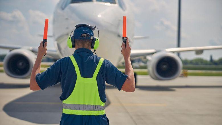 Marshaller sedang bekerja memarkir pesawat