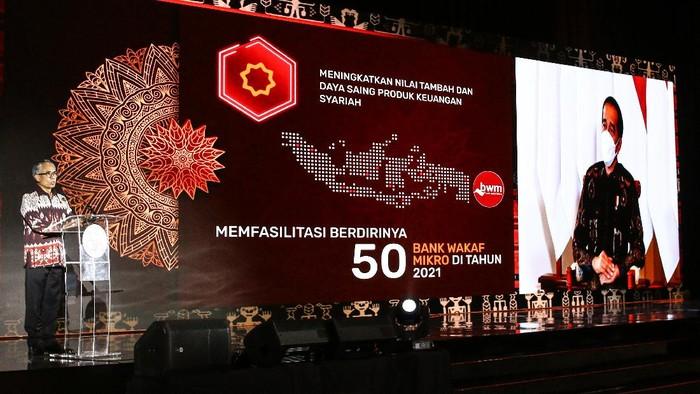 Ketua Dewan Komisioner OJK Wimboh Santoso (kiri) memberikan sambutan yang disaksikan secara virtual oleh Presiden Joko Widodo (kanan) saat pertemuan tahunan OJK di Jakarta, Jumat (15/1/2021). OJK sudah menyiapkan berbagai kebijakan stimulus lanjutan untuk tetap menjaga industri jasa keuangan dan meningkatkan kontribusinya dalam mendorong serta memulihkan perekonomian nasional yang termuat dalam Masterplan Sektor Jasa Keuangan Indonesia (MPSJKI) 2021  2025. ANTARA FOTO/Rivan Awal Lingga/foc.