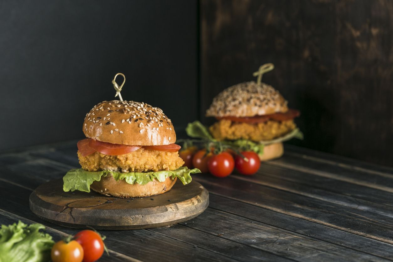 Classic Burger with chicken in a bun with sesame tomatoes, lettuce and mustard sauce. Dark background with copy space. Horizontal orientation. Fast food, takeaway