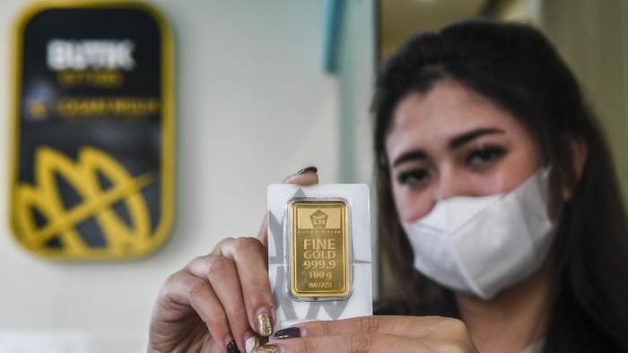 Karyawan menunjukan emas batangan di Butik Emas Antam, Kebon Sirih, Jakarta, Senin (18/1/2021). Harga emas PT Aneka Tambang (Persero) Tbk pada Senin (18/1) berada pada posisi Rp 944.000 per gram atau turun Rp4.000 dari perdagangan akhir pekan lalu. ANTARA FOTO/Galih Pradipta/rwa.