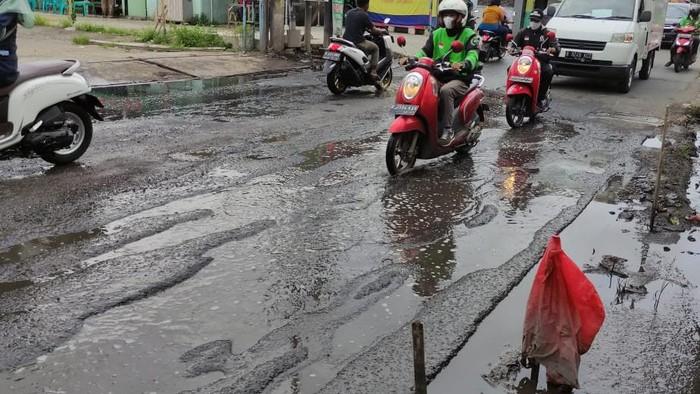 Jalan Caman Raya rusak berlubang hingga digenangi air selokan.