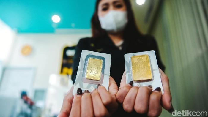 Petugas menunjukan emas imitasi di gerai Antam di kawasan Jakarta Pusat, Senin (18/1/2021). Hari ini saham ANTM turun cukup dalam hingga 6,73%.