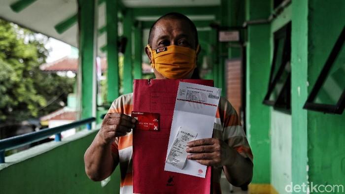 Petugas Bank DKI Jakarta melayani warga untuk pemberian Bantuan Sosial Tunai Pemprov DKI Jakarta dengan dibuatkan buku tabungan bansos Jakarta di  SMKN 12,Tanjung Priok, Jakarta Utara, Senin (18/1). Pemberian BST dengan nominal Rp. 300.000 per orang ini merupakan bantuan dari Pemprov DKI Jakarta untuk membantu warga yang terdampak pandemi COVID-19.  Nantinya uang tersebut akan ditransfer ke rekening warga yang bersangkutan.