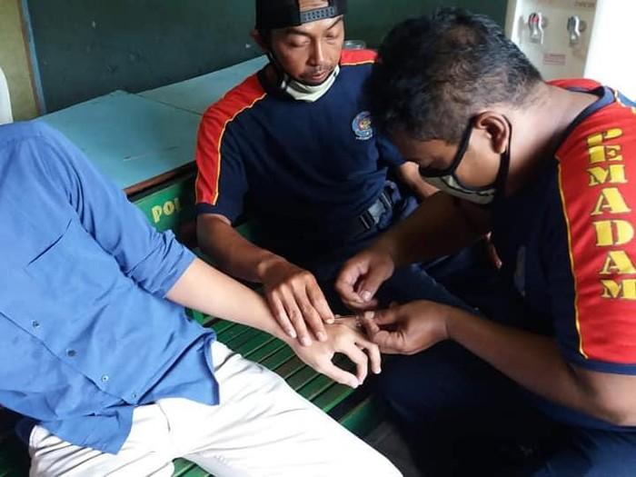 Petugas Damkar Sragen berusaha melepas cincin dari jari warga yang membutuhkan bantuan.