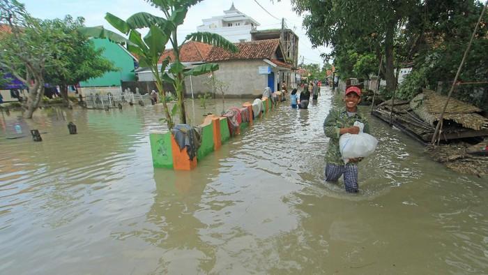Warga berjalan menerobos banjir yang merendam Desa Suranenggala Lor, Kecamatan Suranenggala, Kabupaten Cirebon, Jawa Barat, Selasa (19/1/2021). Banjir akibat luapan sungai dan tingginya intensitas hujan di kawasan itu membuat ratusan rumah warga terendam banjir setinggi 50 sentimeter hingga satu meter. ANTARA FOTO/Dedhez Anggara/wsj.