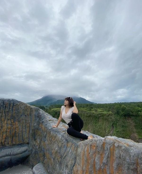 Dinar Candy saat berpose dengan latar Gunung Merapi di Yogyakarta.