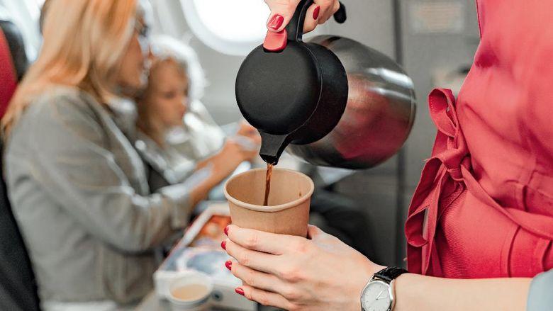 Pramugari melayani secangkir kopi untuk penumpang di pesawat