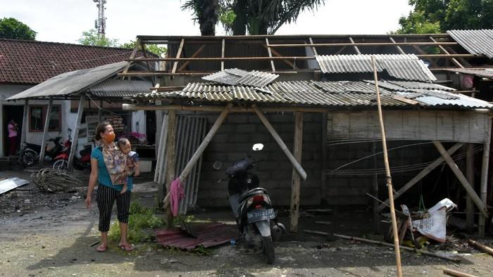 Warga melihat kondisi atap rumah kos yang rusak akibat diterpa angin puting beliung di Desa Pecatu, Badung, Bali, Kamis (21/1/2021). Angin puting beliung yang terjadi disaat hujan deras sekitar pukul 06.00 WITA tersebut merusak puluhan atap rumah kos dan warung serta tidak ada korban jiwa ataupun luka-luka dalam kejadian itu. ANTARA FOTO/Nyoman Hendra Wibowo/foc.