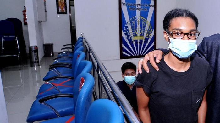 Petugas Imigrasi mengawal warga negara Amerika Serikat Saundra Michelle Alexander (kanan) yang merupakan rekan dari Kristen Antoinette Gray saat akan menuju ke Bandara Internasional I Gusti Ngurah Rai di Kantor Imigrasi Kelas I TPI Denpasar, Bali, Rabu (20/1/2021). Kristen Gray yang cuitannya viral di akun Twitter @kristentootie berupa ajakan bagi orang asing untuk pindah ke Bali pada masa pandemi COVID-19 dan diduga telah menyebarkan informasi lain yang dianggap dapat meresahkan masyarakat dideportasi bersama Saundra Michelle ke Amerika Serikat karena diduga melanggar pasal 75 ayat 1 Undang-undang Nomor 6 Tahun 2011 tentang Keimigrasian. ANTARA FOTO/Fikri Yusuf/wsj.