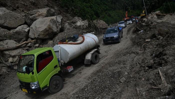 Sejumlah kendaraan melintas di Jalan Trans Sulawesi Poros Majene-Mamuju yang terkena longsor di Majene, Sulawesi Barat, Rabu (20/1/2021). Jalur yang sempat terputus akibat longsor tersebut sudah bisa dilalui dengan sistem buka tutup arus kendaraan dari dua arah. ANTARA FOTO/Sigid Kurniawan/hp.