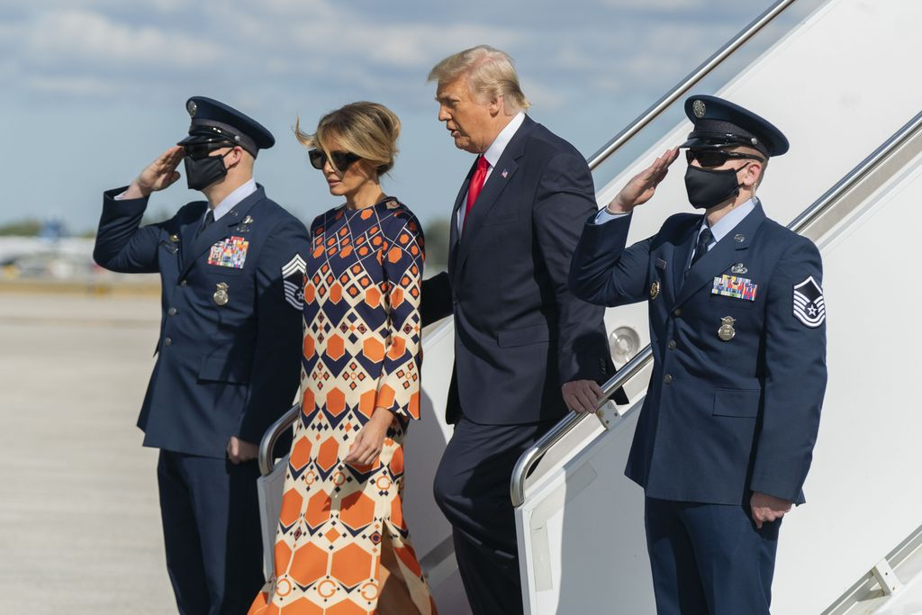 Former President Donald Trump and Melania Trump wave as they disembark from their final flight on Air Force One at Palm Beach International Airport in West Palm Beach, Fla., Wednesday, Jan. 20, 2021. (AP Photo/Manuel Balce Ceneta)