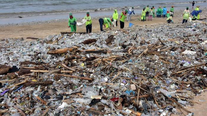 Sejumlah relawan membersihkan sampah kiriman di Pantai Kedonganan, Badung, Bali, Kamis (21/1/2021). Sampah kiriman akibat cuaca ekstrim yang memenuhi kawasan pantai di Kabupaten Badung tersebut dibersihkan secara bertahap. ANTARA FOTO/Nyoman Hendra Wibowo/hp.